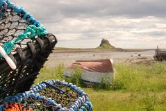 Harbour bay at Lindisfarne with castle & lobster pots. Lindisfarne harbour bay & castle with lobster pots and boat stock images