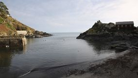Harbour and coast entrance to Polperro Cornwall South West England UK smooth professional video pan stock footage
