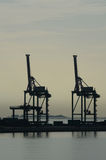 Harbour Container Cranes Silhouette. At seaside with reflection in water Royalty Free Stock Photography