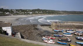 Harbour in Cornwall with waves rolling in boats and beach Royalty Free Stock Images