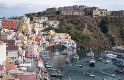 The harbour at Corricella fishing village with pastel coloured houses on the island of Procida Italy, photographed from the cliff. stock photo