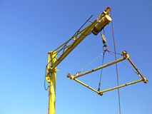 Harbour crane. Close up of the yellow harbour crane on the blue sky. Crane used to lifting yachts and motor boats Royalty Free Stock Photography