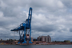Harbour crane standing idle under cloudy sky Royalty Free Stock Image