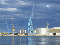 Mobile cranes and tanks at an industrial port in the evening. Evening light on the mobile dock cranes in the commercial port of Sete, France stock image