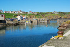 The harbour entrance, boats and village at St. Abbs, Berwickshir Royalty Free Stock Image
