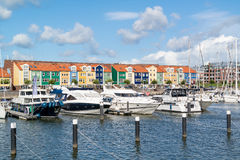Harbour in Hellevoetsluis, Netherlands. Colourful facades of houses and motor yachts in marina Hellevoetsluis, Netherlands stock images