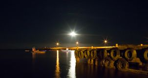 Harbour Lights with full moon rising at fishing harbor. Harbour lights with full moon rising in South Africa. The harbour of the most Southern Tip of Africa at stock image