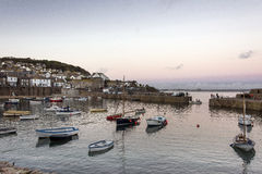 The harbour at Mousehole. Mousehole a tourist destination in Cornwall, United Kingdom  showing the harbour entrance with many small boats moored within it and Royalty Free Stock Image