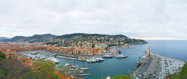 The harbour of Nice. NICE, FRANCE - FEBRUARY 21, 2012: The Castle Hill overlooks the best view on the Lympia port, surrounded by colorful buildings and green Royalty Free Stock Photos