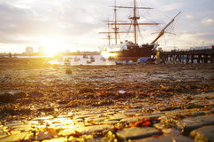 Sunset over HMS Warrior in Portsmouth Harbour. Golden sunset over Portsmouth Harbour showing HMS Warrior in Middle Distance and Cobblestones in Foreground Stock Images