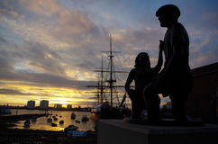 Harbour Sunset. Golden sunset over Portsmouth Harbour showing HMS Warrior and Mudlarks Statue Royalty Free Stock Photo