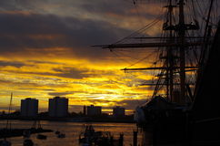 Harbour Sunset. Golden sunset over Portsmouth Harbour showing HMS Warrior in silhouette Stock Image
