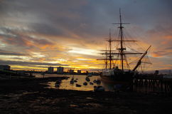 Sunset over HMS Warrior in Portsmouth Harbour. Golden sunset over Portsmouth Harbour showing HMS Warrior in silhouette Stock Photo
