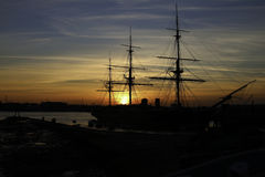 Harbour Sunset. The sun sets behind HMS Warrior (1860) in Portsmouth Harbour, England, UK Stock Photos