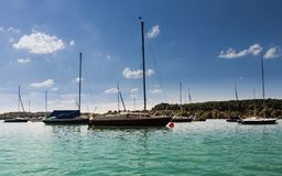 Harbour of Wörthsee with many beautiful boats, masts and water plants.. Different vessel for water sports are ready. Taken from stock image