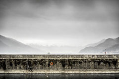 A harbour wall on Lake Como with a ferry and snow capped hills in the background. Stock Photo