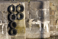 Harbour wall and tyres. An old harbour wall with hanging tyres Royalty Free Stock Image