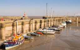 The harbour at Watchet in Somerset in autumn sunlight. With boats moored at low tide, water reflections on the sand and harbour light in the distance stock photography