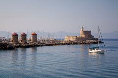 Harbour Windmills & Lighthouse St. Nicholas, Rhodes. The famous landmark of Rhodes, Greece is the lighthouse, the first of many historical buildings seen by stock photography