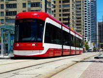 Red streetcar in Toronto with concrete condominiums royalty free stock photo