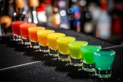 Hard alcoholic shots. A row of hard alcoholic shots in rainbow colours served on the bar counter Stock Photos