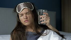 Hard awakening of a woman after excessive alcohol consumption. Headache, dry mouth, nausea. Hangover Syndrome.