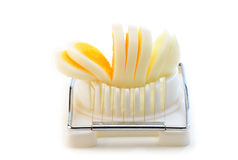 Hard boiled egg sliced. Hard boiled egg in slicer on white background with room for text Stock Image