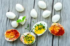 Hard Boiled Eggs. Bio Fresh hard boiled eggs ,mozzarella cheese and fresh basil sliced and broken with  onion and red pepper on wooden background Royalty Free Stock Photos
