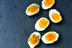 Hard Boiled Eggs. Bio Fresh hard boiled eggs sliced and broken with  onion  on black background Stock Photo