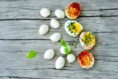 Hard Boiled Eggs. Bio Fresh hard boiled eggs ,mozzarella cheese and fresh basil sliced and broken with  onion and red pepper on wooden background Stock Image