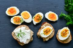 Hard Boiled Eggs and Sandwiches. Bio Fresh hard boiled eggs sliced and broken with onion on black background .Sandwiches with soft cream cheese and whole grain royalty free stock image