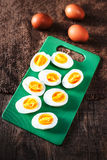 Hard boiled eggs, sliced in halves on cutting board wooden backg Royalty Free Stock Image