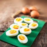 Hard boiled eggs, sliced in halves on cutting board wooden backg Stock Images