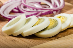 Hard boiled eggs sliced with red onion Royalty Free Stock Photos