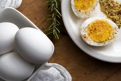 Hard boiled eggs. Whole and halved dard boiled eggs with mustard Royalty Free Stock Photography