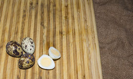 Hard boiled quail egg halves with egg shells on wooden board, photographed with natural light Selective Focus Royalty Free Stock Image