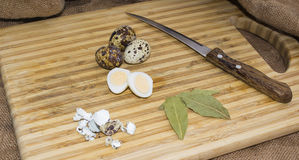 Hard boiled quail egg halves with egg shells on wooden board, photographed with natural light Selective Focus Royalty Free Stock Photos