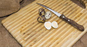 Hard boiled quail egg halves with egg shells on wooden board, photographed with natural light Selective Focus Royalty Free Stock Photo