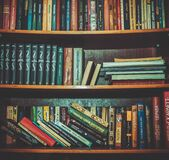 Hard Bound Books on Brown Wooden Shelf Royalty Free Stock Image