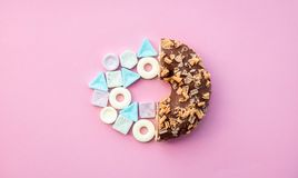 Hard candy and chocolade donut. On pink background. Above view royalty free stock photo