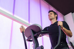 Hard Cardio in Elliptical. Handsome man training cardio with elliptical machine in gym Royalty Free Stock Photography