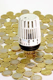 Hard cash. Thermostat with euros hard cash in background royalty free stock photography
