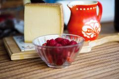 Hard cheese, raspberry and rustic red jug. Big piece of spicy hard cheese, raspberry in glass bowl and red old pitcher with flower ornaments on kitchen board on Stock Image