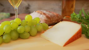 Hard cheese with white wine. grapes and bread stock footage