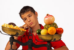 Hard choice. Teenager badly wanting junk food instead healthy one Royalty Free Stock Photography