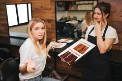 Hard choise Confused blonde young woman can`t choosing color hair from palette before coloring in beauty salon. Beauty royalty free stock photo