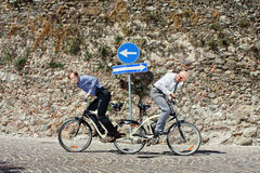 Hard competition. Two men pulling the bicycle in their own direction and trying hard to win the competition Stock Image