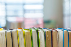 Hard covered library books on shelf with blurred background Stock Photo