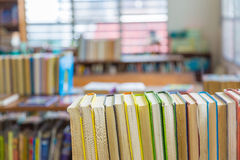 Hard covered library books on shelf with blurred background Royalty Free Stock Photography
