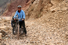 Hard Cycling. Cycling through remote mountain road in Tibet stock images